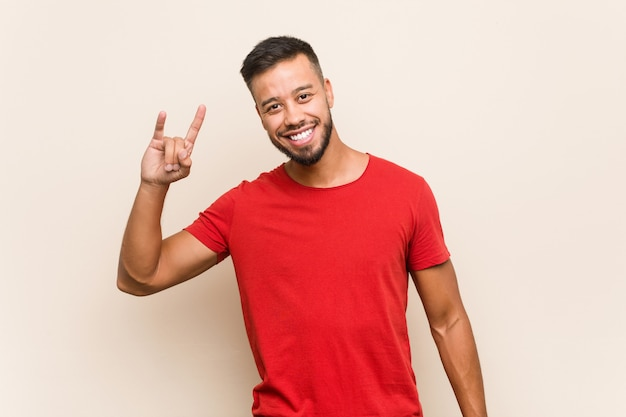 Young south-asian man showing a horns gesture as a revolution concept.