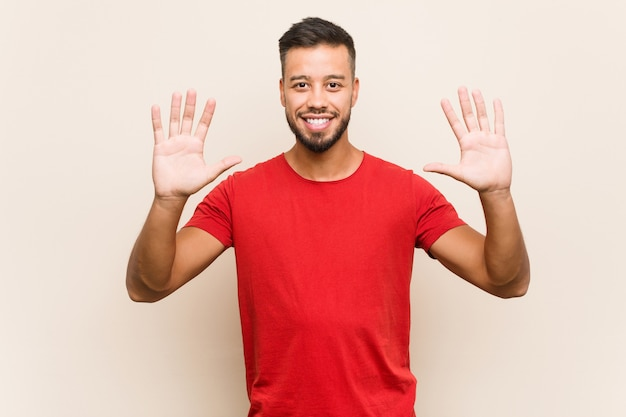 Young south-asian man showing number ten with hands.