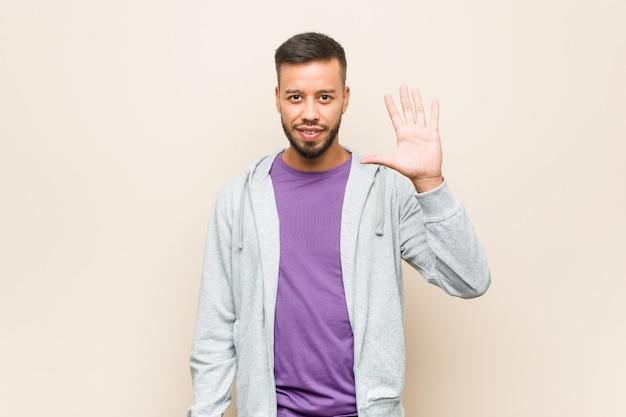 Молодой человек из южной азии, улыбаясь, весело показывает номер пять пальцами.