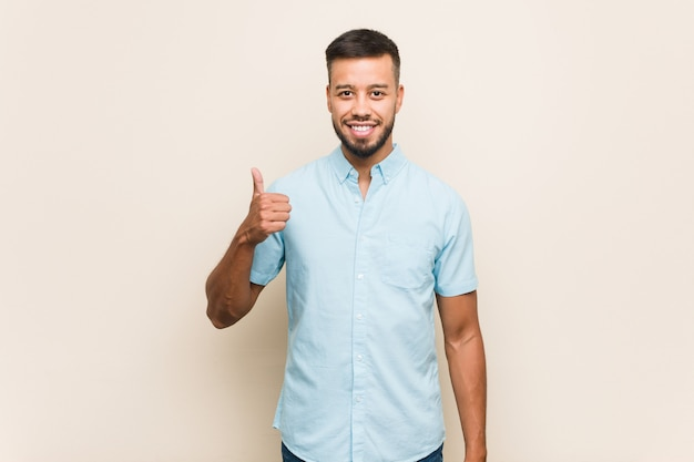 Young south-asian man smiling and raising thumb up