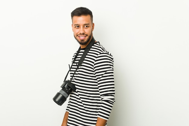 Young south-asian photographer looks aside smiling, cheerful and pleasant.