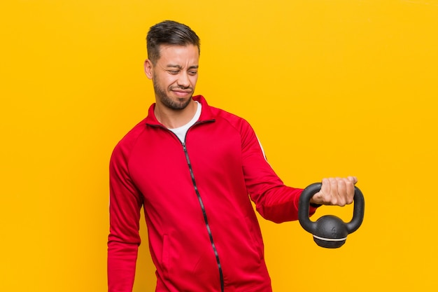 Young south-asian sport man holding a dumbbell