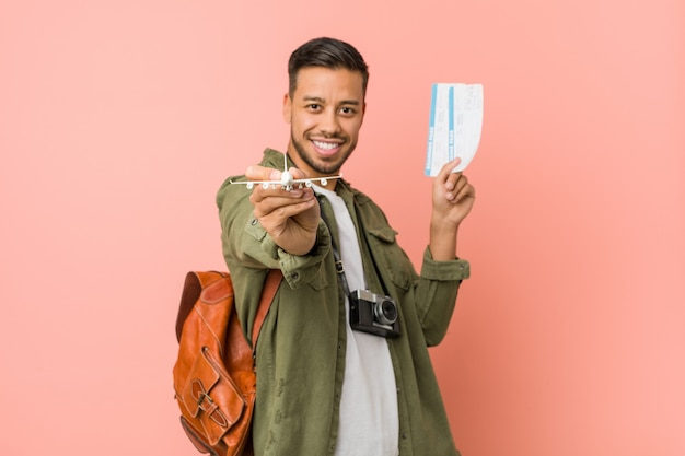 Young south asian traveler holding an air tickets.