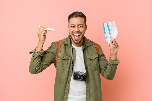 Young south-asian traveler holding an air tickets.