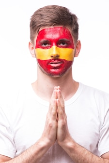 Appassionato di calcio del giovane uomo spagnolo con gesto di preghiera isolato sulla parete bianca