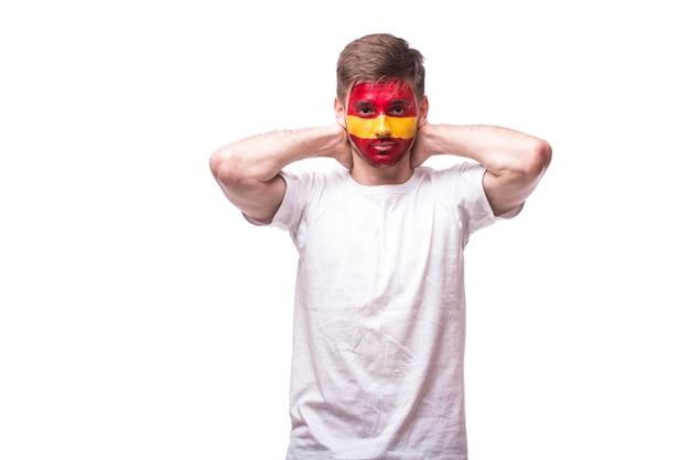 Молодой испанский футбольный фанат с грустным жестом, изолированным на белой стене