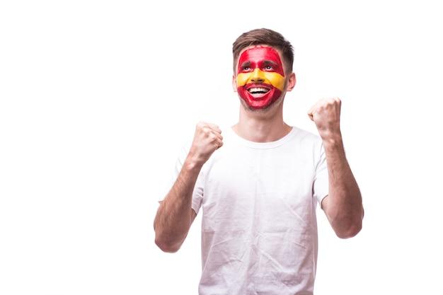 Молодой испанский болельщик футбола с жестом победы, изолированные на белой стене