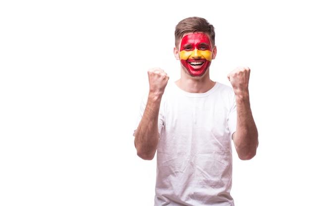 Appassionato di calcio del giovane uomo spagnolo con il gesto di vittoria isolato sul muro bianco