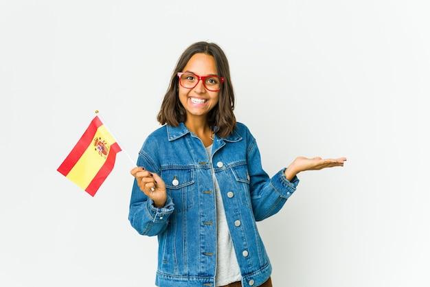 Молодая испанская женщина, держащая флаг, изолированный на белом, взволнована, держа копию пространства на ладони.