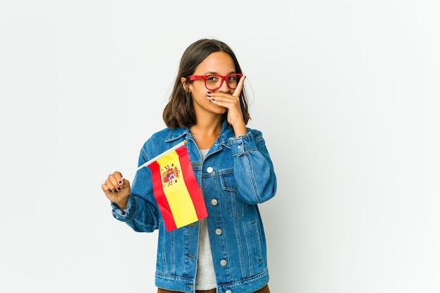 Молодая испанская женщина держит флаг, изолированный на белом, пряча глаза сквозь пальцы, смущенно закрывая лицо.