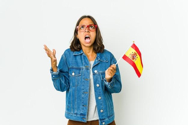 Молодая испанская женщина, держащая флаг, изолированный на белом, кричала в небо, глядя вверх, разочарованная.