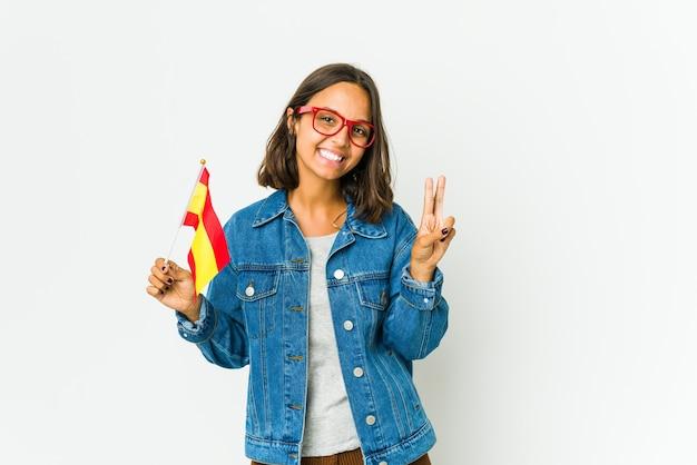 Молодая испанская женщина, держащая флаг, изолированные на белом, показывает знак победы и широко улыбается.