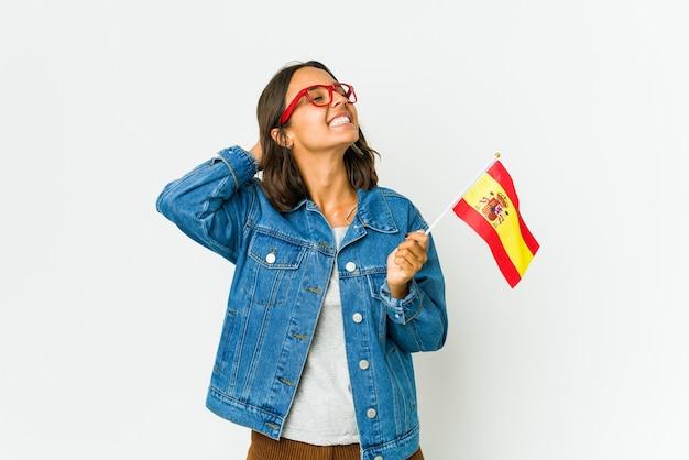 頭の後ろに手を置いて、自信を持って白い壁に隔離された旗を保持している若いスペインの女性。