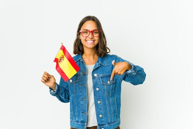 白い壁に隔離された旗を持っている若いスペインの女性は、指で下向き、前向きな気持ち。