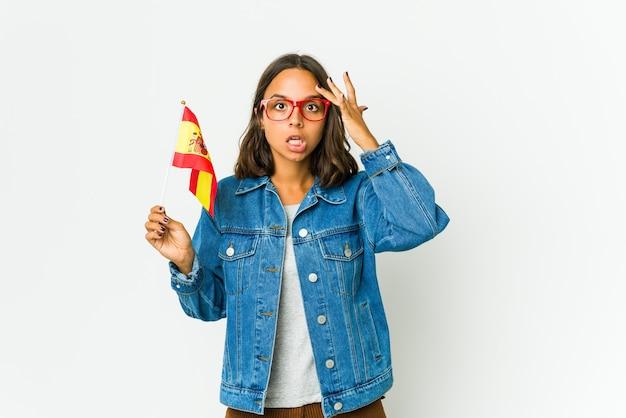 白い壁に隔離された旗を保持している若いスペインの女性は大声で叫び、目を開いたままにし、手を緊張させます