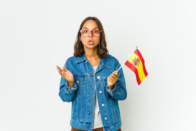 白い壁に隔離された旗を持っている若いスペインの女性は驚いてショックを受けました。