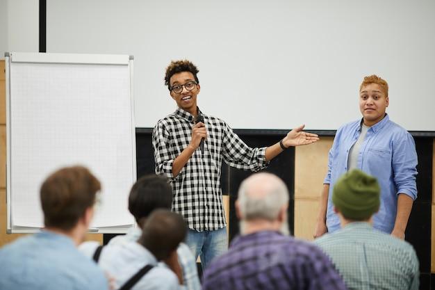 Молодой оратор разговаривает с аудиторией на конференции