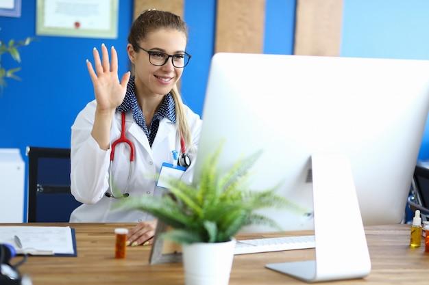 若い専門家がコンピューターモニターの前に座って、オンラインで患者に挨拶する