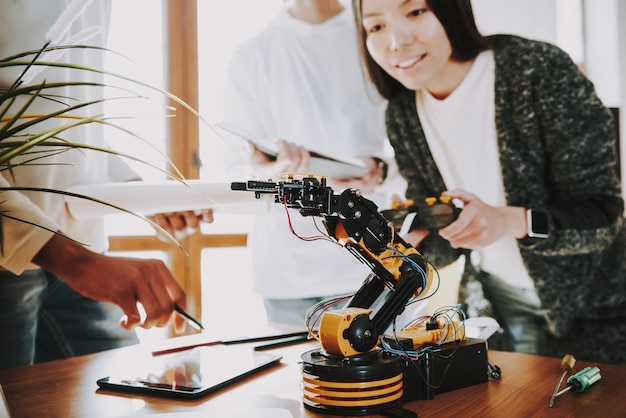 Young specialists with robot at work.