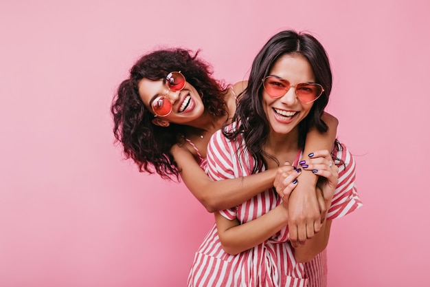 Modelle giovani e spettacolari posano vigorosamente per il ritratto. sorelle abbronzate si abbracciano e ridono con occhiali insoliti.