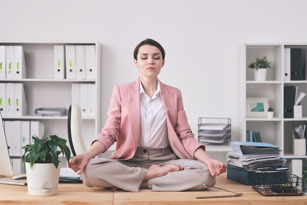 Young spiritual woman in pink jacket sitting in lotus position on table and meditating in office