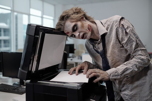 Молодой жуткий бизнесмен с рисунком зомби на лице и руках, склонившийся над ксероксом, делая копии документов