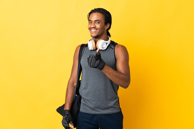 엄지 손가락 제스처를주는 노란색 배경에 고립 가방 머리 띠와 젊은 스포츠 아프리카 계 미국인 남자