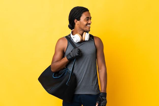 측면을 찾고 노란색 배경에 고립 가방 머리 띠와 젊은 스포츠 아프리카 계 미국인 남자
