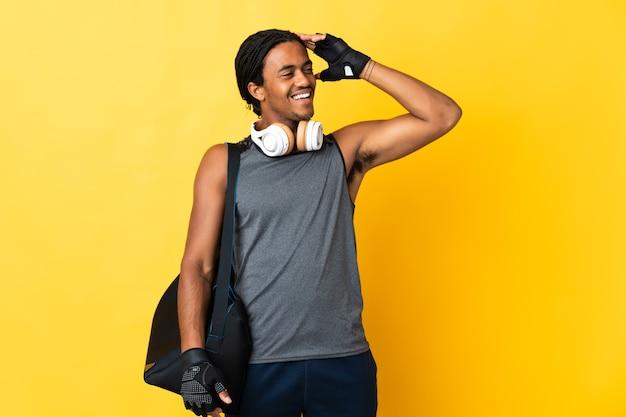 많이 웃 고 노란색 배경에 고립 된 가방 머리 띠와 젊은 스포츠 아프리카 계 미국인 남자