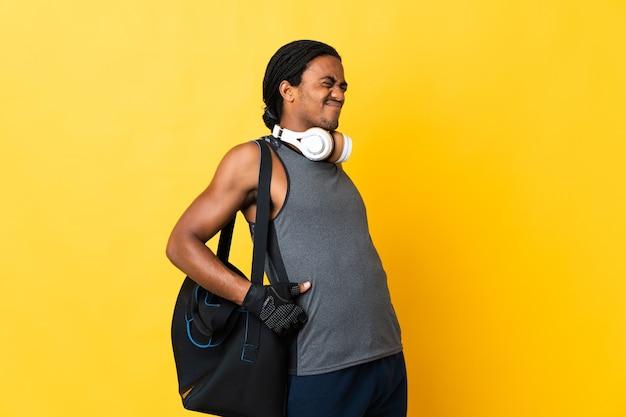 노력을 한 데 대한 요통으로 고통받는 노란색 배경에 고립 된 가방 머리띠와 젊은 스포츠 아프리카 계 미국인 남자