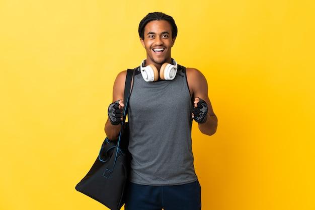 勝者の位置での勝利を祝う黄色の壁に分離されたバッグと三つ編みの若いスポーツアフリカ系アメリカ人の男