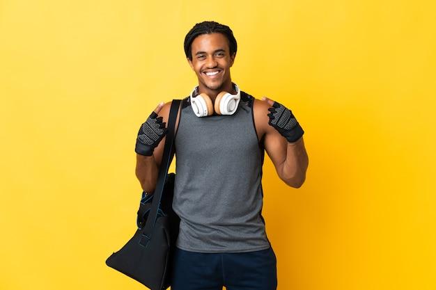 엄지 손가락 제스처를주는 노란색 벽에 고립 된 가방 머리 띠와 젊은 스포츠 아프리카 계 미국인 남자