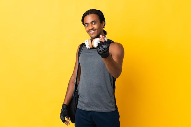 Молодой спортивный афро-американский мужчина с косами с сумкой, изолированной на желтой стене, делает денежный жест
