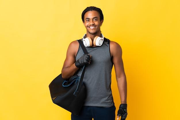 Молодой спортивный афро-американский мужчина с косами с сумкой, изолированной на желтой стене, позирует с руками на бедрах и улыбается