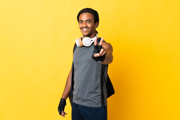 Young sport african american man with braids with bag isolated on yellow background smiling and showing victory sign