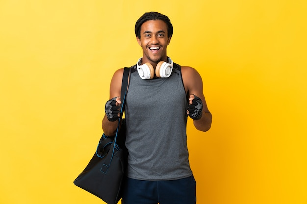 Young sport african american man with braids with bag isolated on yellow wall celebrating a victory in winner position