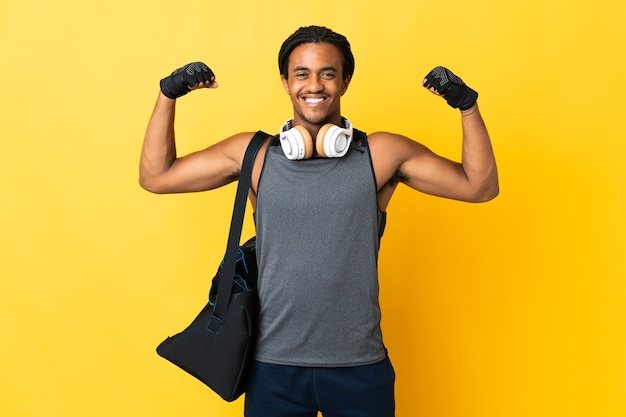 Young sport african american man with braids with bag isolated on yellow wall doing strong gesture