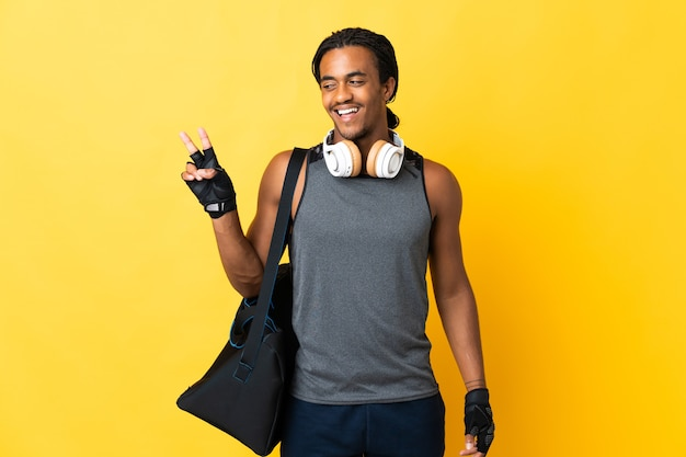 Young sport african american man with braids with bag isolated on yellow wall smiling and showing victory sign