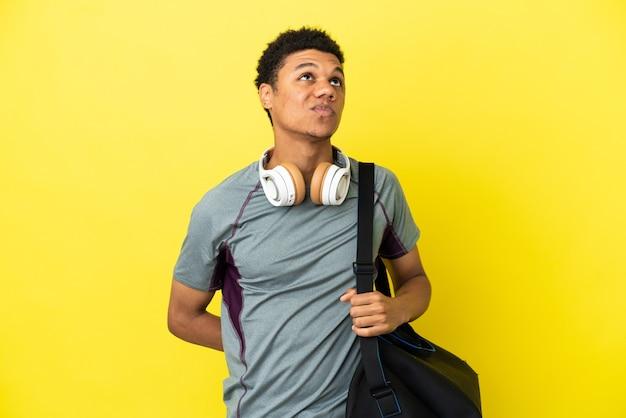 Молодой спортивный афро-американский мужчина со спортивной сумкой, изолированной на желтом фоне и смотрящей вверх