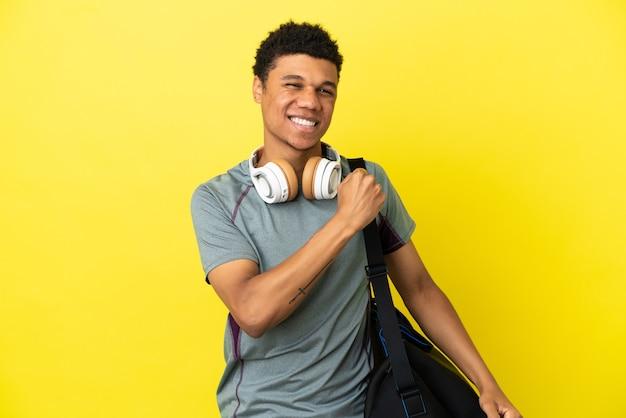 勝利を祝う黄色の背景に分離されたスポーツバッグを持つ若いスポーツアフリカ系アメリカ人の男