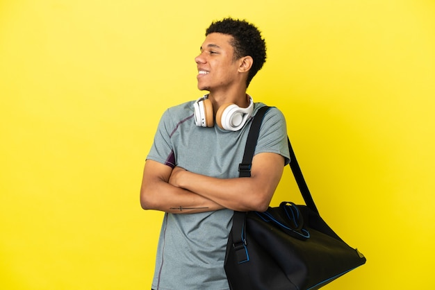 Молодой спортивный афро-американский мужчина со спортивной сумкой, изолированной на желтом фоне, счастлив и улыбается