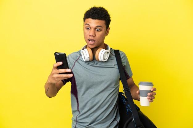 노란색 배경에 격리된 스포츠 가방을 들고 테이크아웃 커피와 모바일을 들고 있는 젊은 스포츠 아프리카계 미국인 남자