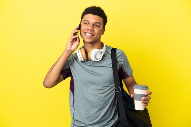 Молодой спортивный афро-американский мужчина со спортивной сумкой, изолированной на желтом фоне, держит кофе на вынос и мобильный