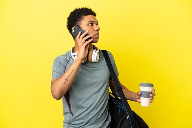 持ち帰り用のコーヒーと携帯電話を保持している黄色の背景に分離されたスポーツバッグを持つ若いスポーツアフリカ系アメリカ人の男