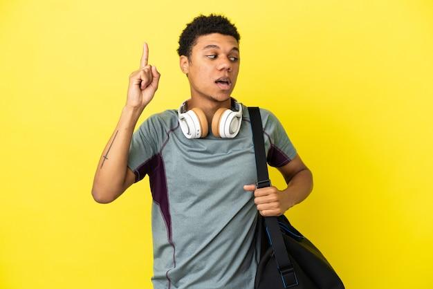 Молодой спортивный афро-американский мужчина со спортивной сумкой, изолированной на желтом фоне, намеревается реализовать решение, поднимая палец вверх