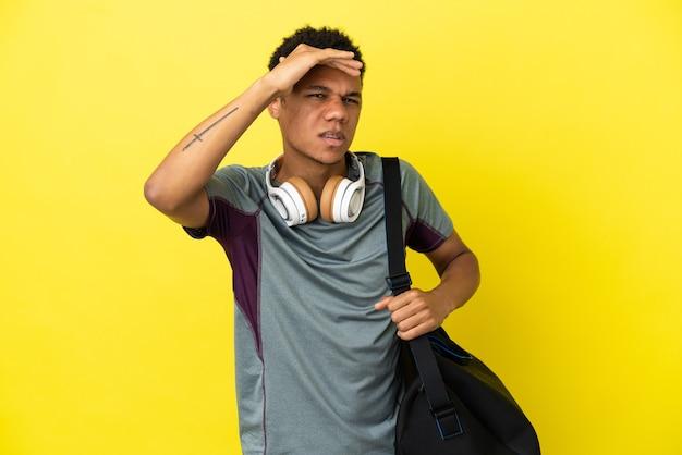 Молодой спортивный афро-американский мужчина со спортивной сумкой, изолированным на желтом фоне, смотрит вдаль с рукой, чтобы что-то посмотреть