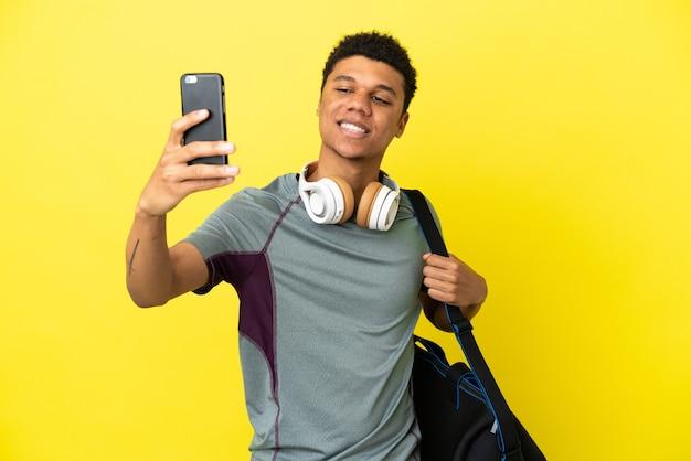 Молодой спортивный афро-американский мужчина со спортивной сумкой, изолированной на желтом фоне, делает селфи