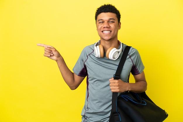 Молодой спортивный афро-американский мужчина со спортивной сумкой на желтом фоне, указывая пальцем в сторону