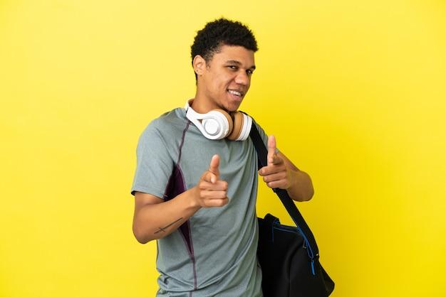 正面を指して笑顔で黄色の背景に分離されたスポーツバッグを持つ若いスポーツアフリカ系アメリカ人の男