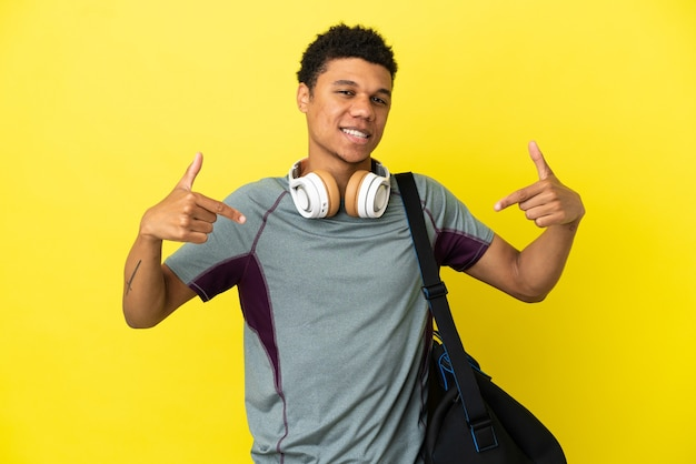 Молодой спортивный афро-американский мужчина со спортивной сумкой, изолированные на желтом фоне, гордый и самодовольный